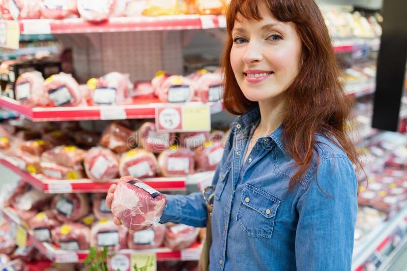 Cliente sonriente que sostiene un pedazo de carne imágenes de archivo libres de regalías