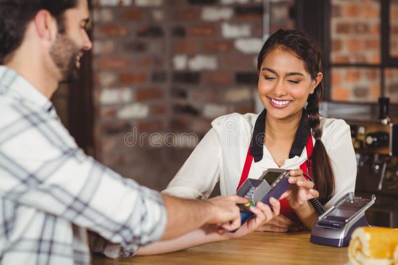 Cliente sorridente che scrive sul terminale del perno immagine stock libera da diritti