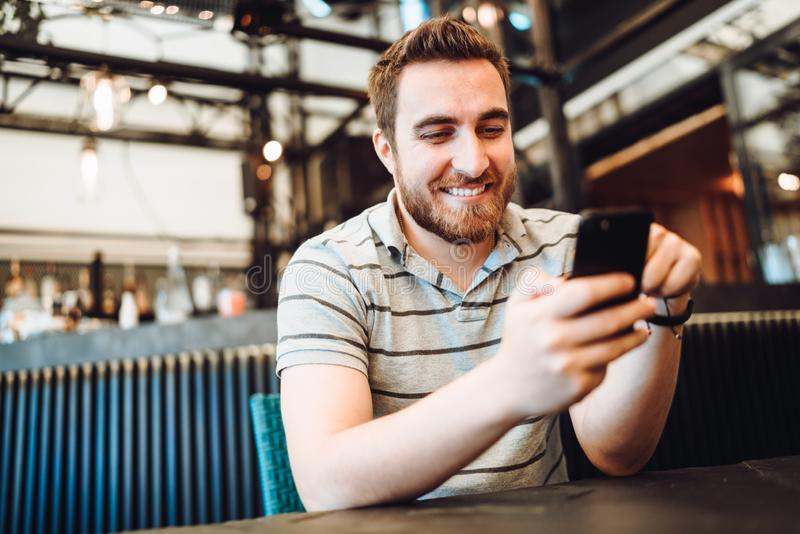 Cliente sorridente felice che paga il pranzo facendo uso di nuova, tecnologia senza contatto moderna con la carta di credito fotografia stock libera da diritti