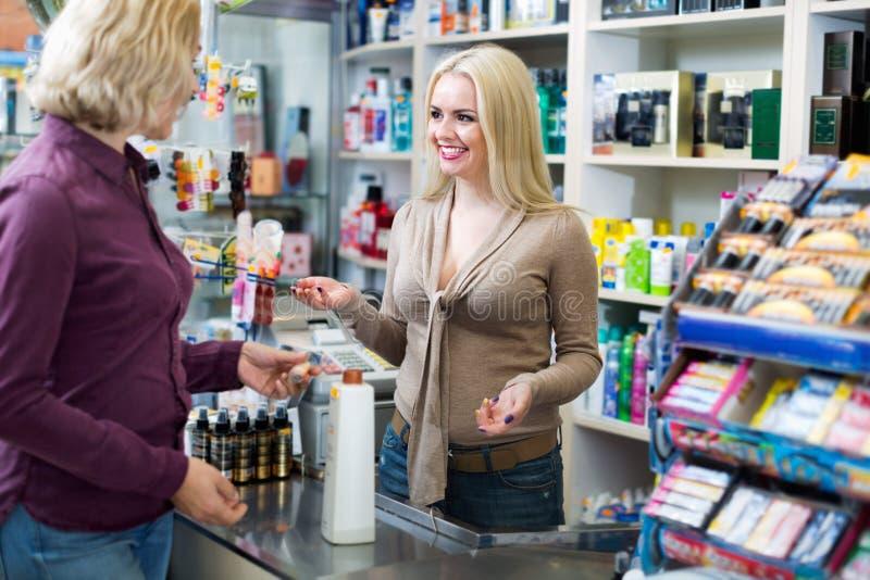 Cliente sorridente positivo al pagamento del negozio immagini stock
