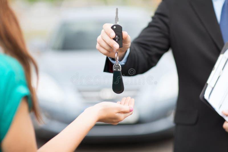 Cliente y vendedor con llave del coche foto de archivo