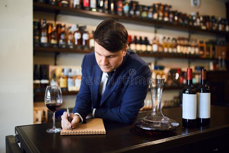 Clientes de ajuda do homem para escolher o vinho correto para uma refeição ou um orçamento foto de stock royalty free