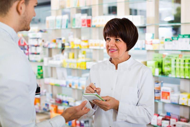 Clientes de ayuda del farmacéutico de la mujer en farmacia foto de archivo