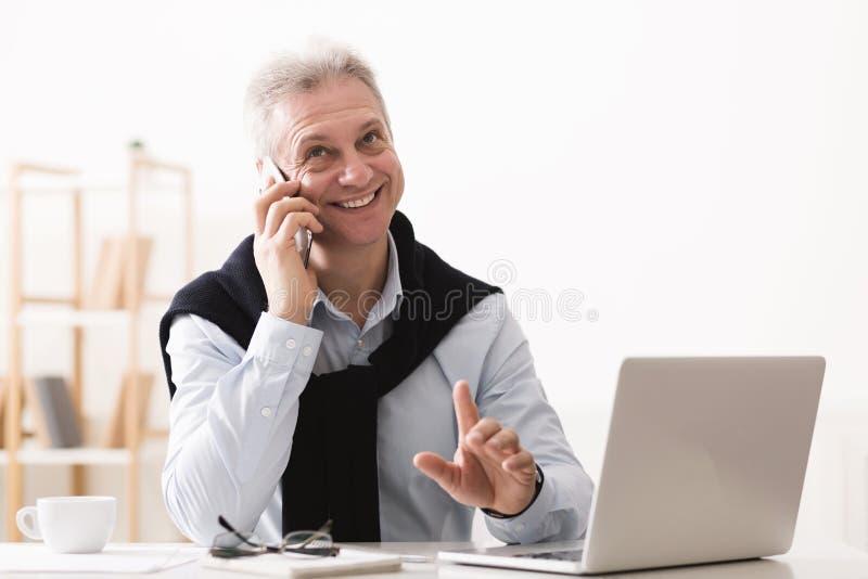 Clientes de consulta do homem de negócios superior executivo, trabalhando no portátil fotografia de stock