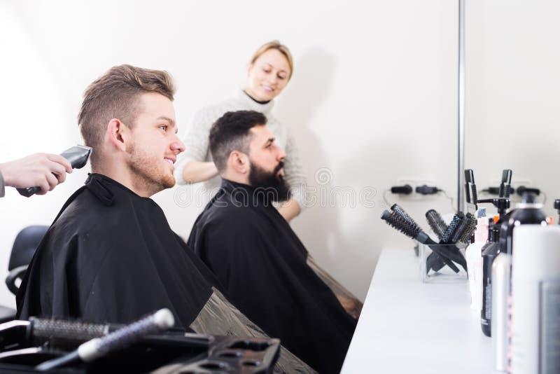Clientes de los hombres jovenes en el salón de pelo imagenes de archivo