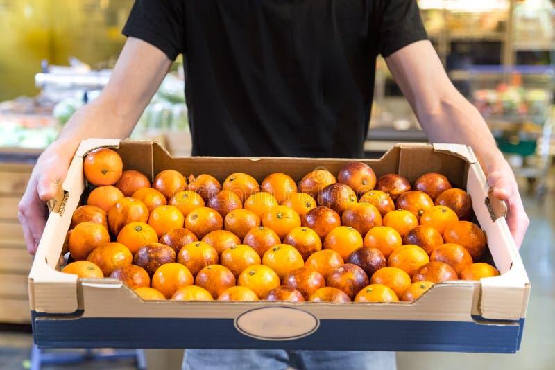 Clientes de sorriso que compram laranjas sicilianos na se??o do mantimento fotos de stock royalty free