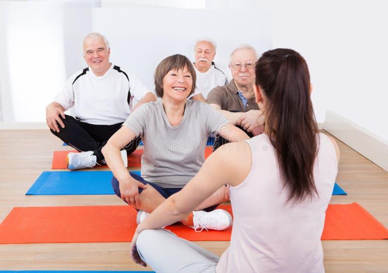 Clientes do treinamento do instrutor na classe da ioga fotos de stock
