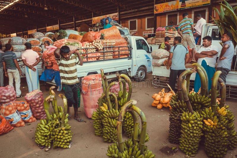 Clientes e comerciantes por atacado do mercado de fruto da vila e muitos sacos dos cocos, banana verde imagens de stock royalty free