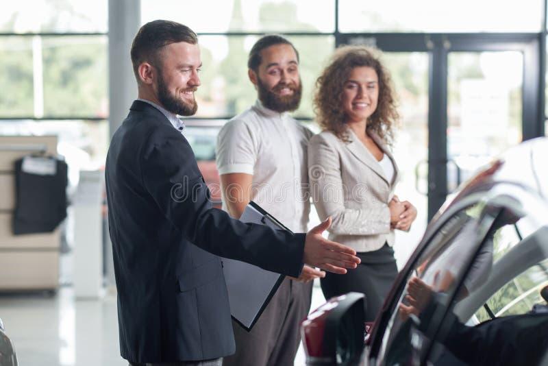 Clientes e concessionário automóvel felizes observando o automóvel fotografia de stock