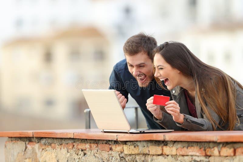 Clientes em linha entusiasmados que encontram ofertas em férias fotografia de stock