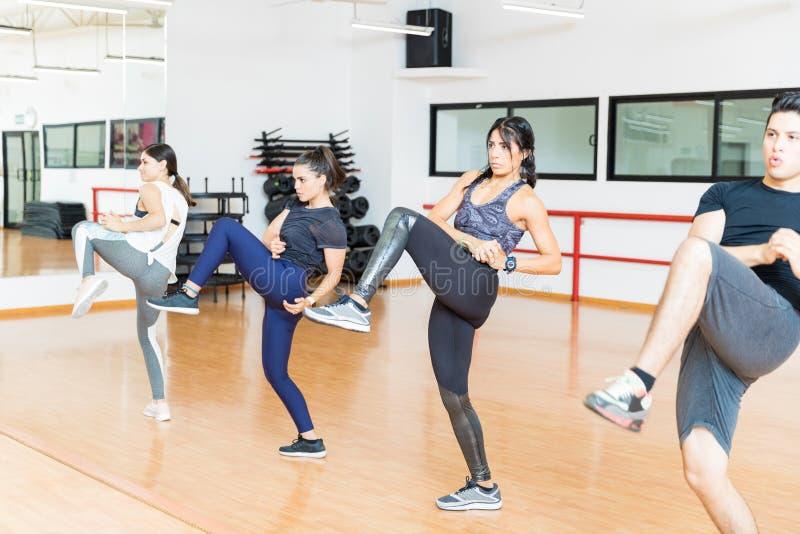 Clientes enfocados que hacen el ejercicio de Kickboxing en club de salud fotos de archivo libres de regalías
