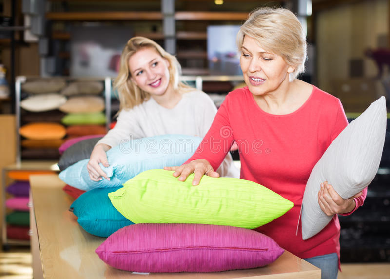 Clientes femeninos jovenes y mayores alegres que miran a través de las almohadas i foto de archivo