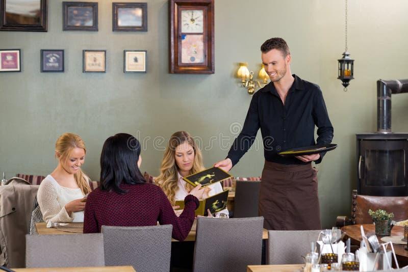 Clientes jovenes de la hembra de Giving Menu To del camarero imagen de archivo