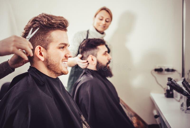 Clientes jovenes que hacen que su pelo sea cortado por los peluqueros fotos de archivo