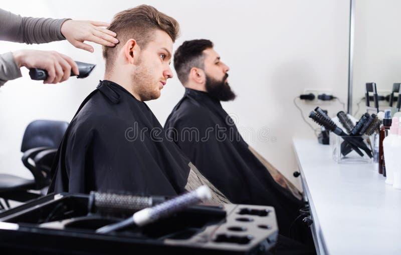 Clientes jovenes que hacen que su pelo sea cortado por los peluqueros fotos de archivo libres de regalías
