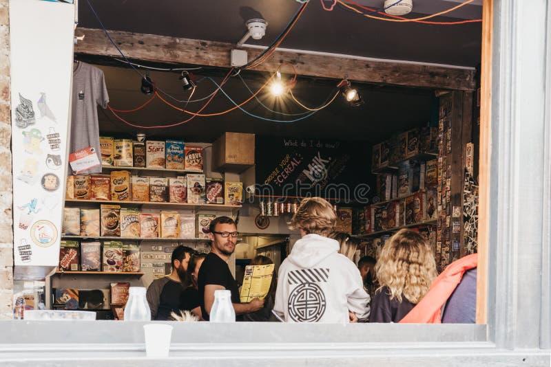 Clientes no assassino do cereal na pista do tijolo, Londres, café internacional do cereal dos mundos o primeiro foto de stock