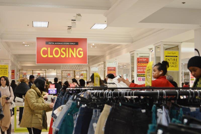 Clientes no senhor e no Taylor New York Shopping Clothes fora dos executivos que compram a mercadoria do desconto imagem de stock