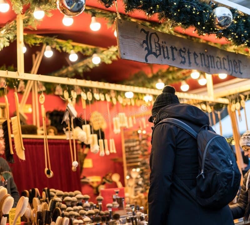 Clientes ocupados do mercado do Natal de Gendarmenmarkt que consultam bens handcrafted na exposição imagens de stock