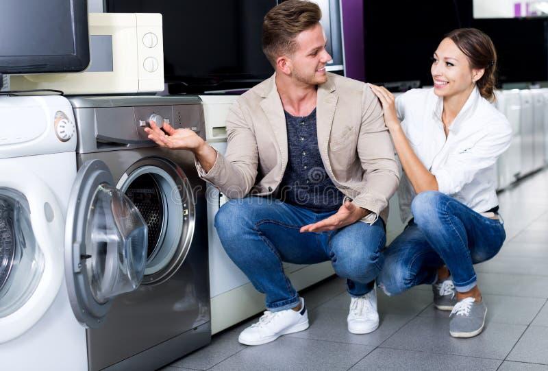 Clientes positivos que olham a máquina da lavanderia imagens de stock