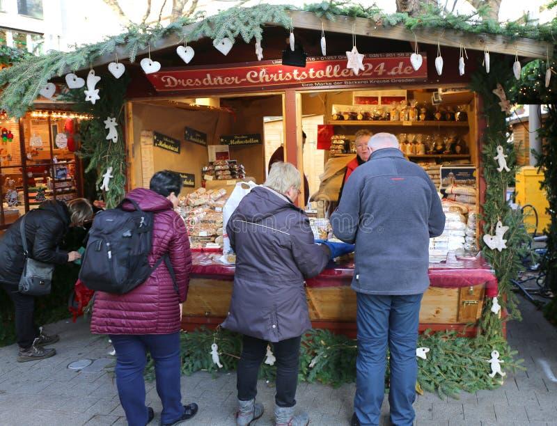 Clientes que compram o bolo tradicional de Dresden no mercado do Natal fotos de stock