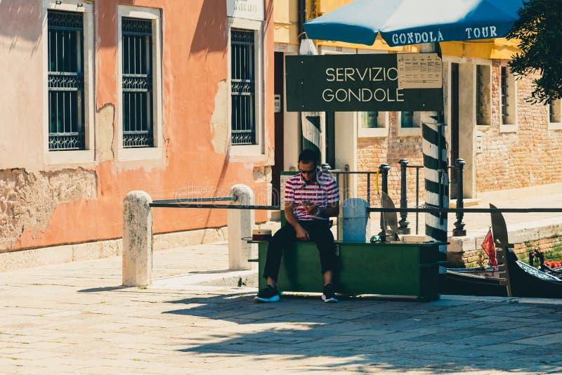 Clientes que esperan del gondolero para un paseo de la góndola en Venecia, Ital fotografía de archivo