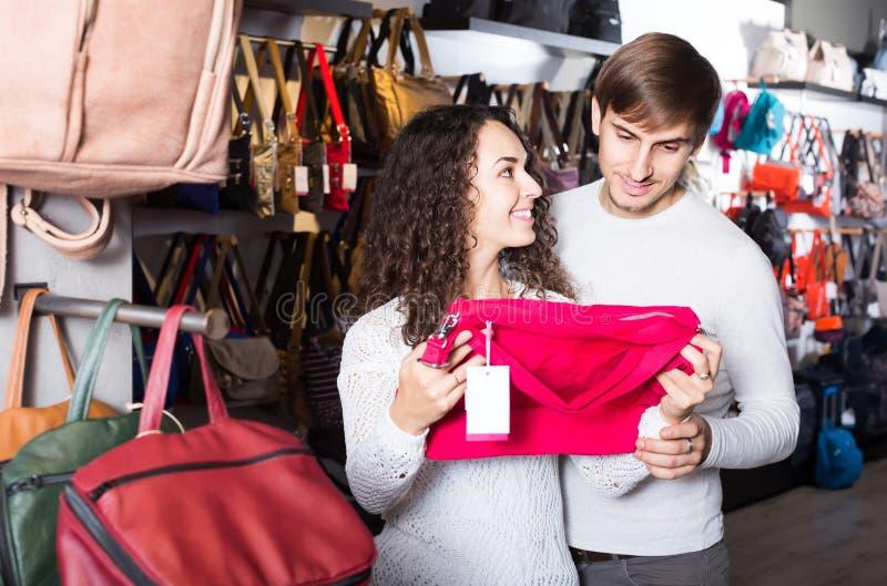 Clientes que miran los bolsos femeninos elegantes en tienda fotografía de archivo libre de regalías
