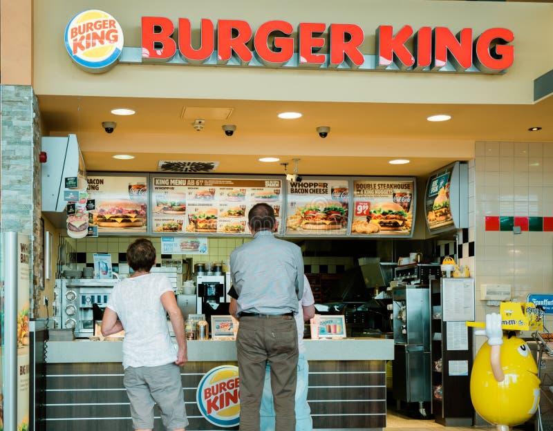 Clientes superiores e adultos no contador do restaurante de Burger King fotografia de stock royalty free