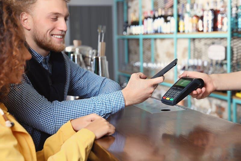 Clienti che per mezzo dello smartphone e del terminale POS di credito per non il pagamento in contanti fotografia stock libera da diritti
