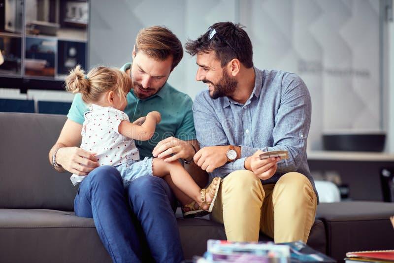 Clienti gay coppia che si divertono nello shopping e si divertono con la loro bambina fotografia stock