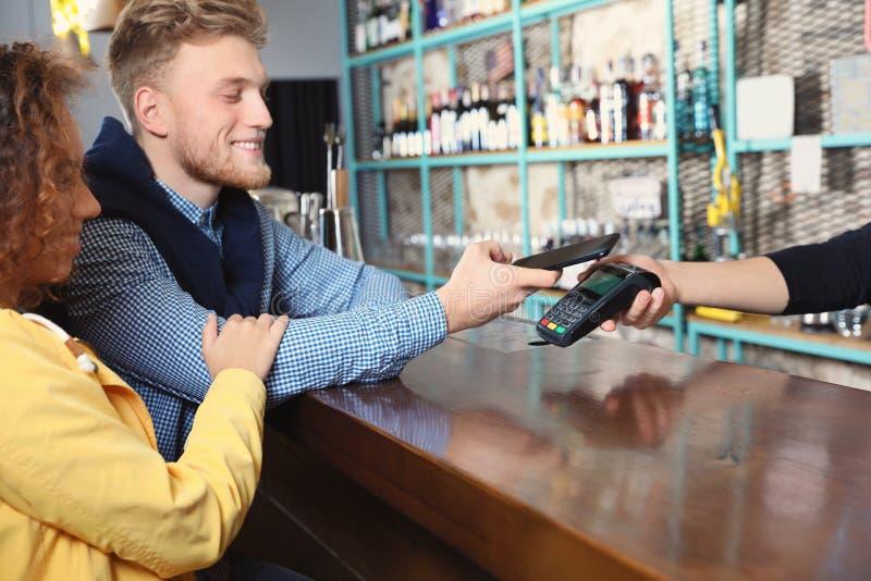Clients à l'aide du smartphone et de la machine de carte de crédit pour le règlement par écritures photo libre de droits