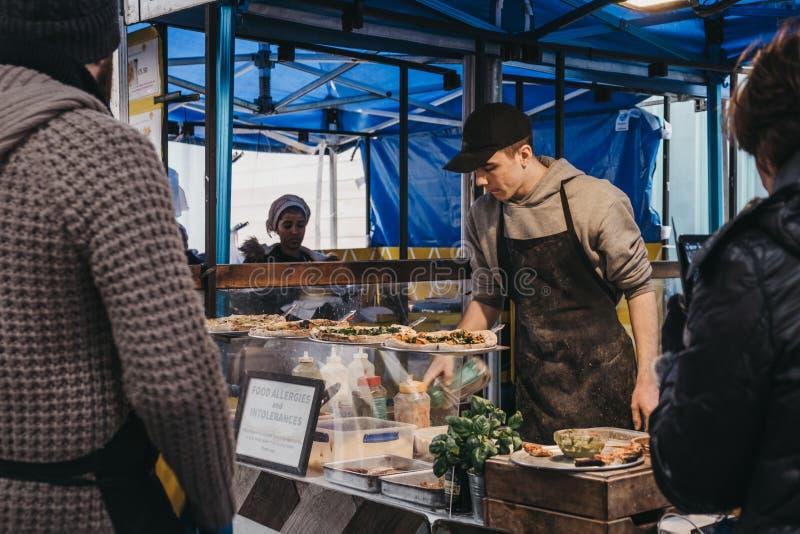 Clients attendant l'ordre à un stand de nourriture de pizza de vegan à l'intérieur de marché de Greenwich, Londres, R-U photo stock
