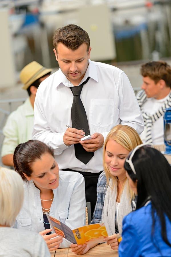 Clients de femmes passant commande du serveur au restaurant images stock