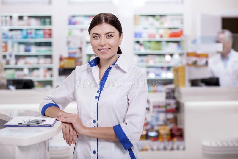 Clients de révision de pharmacien féminin joyeux photographie stock