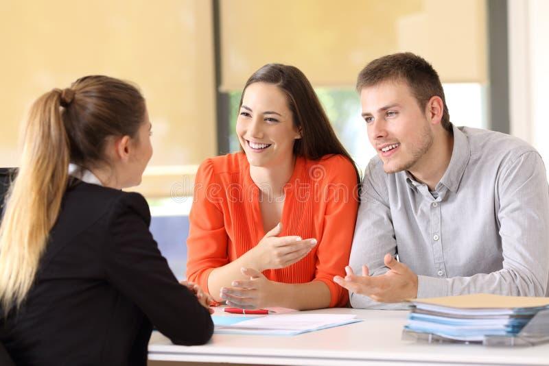 Clients heureux parlant avec l'employé de bureau images libres de droits