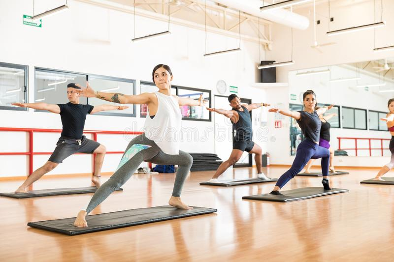 Clients Performing Warrior Pose Ii On In Health Club. Clients performing Warrior II Pose on exercise mat in health club royalty free stock photography