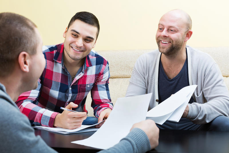 Clients sitting with papers and smiling. Satisfied adult clients sitting at the table with papers and smiling stock photo