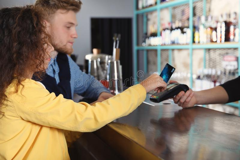 Clients using credit card machine for non cash payment. In cafe stock image