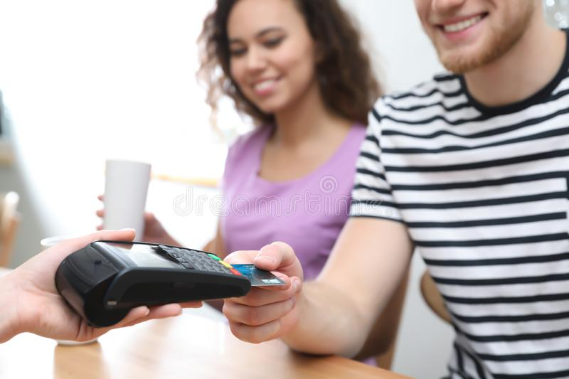 Clients using credit card machine for non cash payment in cafe. Closeup royalty free stock images