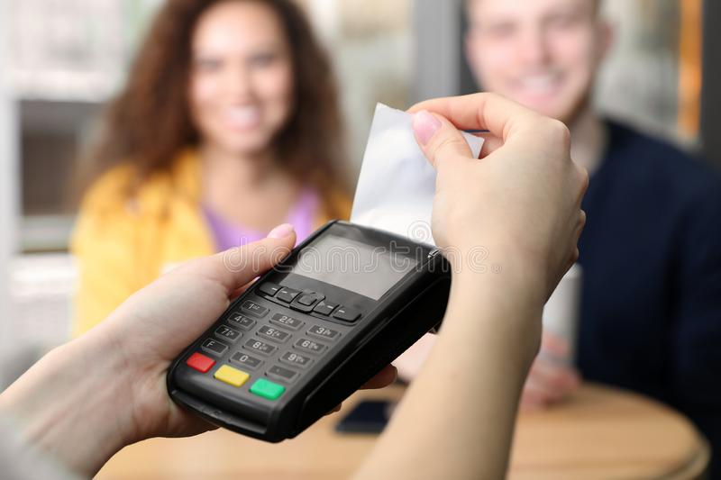 Clients using credit card machine for non cash payment in cafe. Closeup stock photos