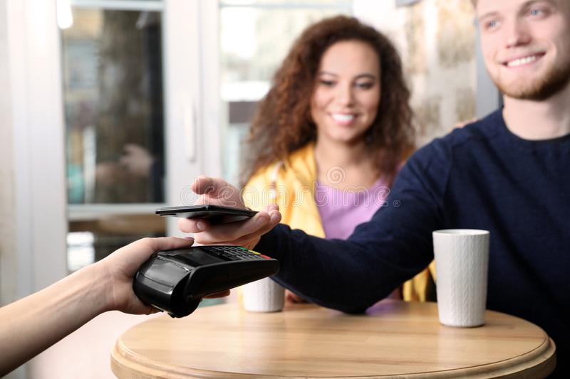 Clients using smartphone and credit card machine for non cash payment. In cafe royalty free stock photos