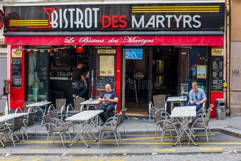 Clients vérifiant leurs téléphones portables comme ils attendent dans les martyres improbable-appelés de DES de Bistros dans  image stock