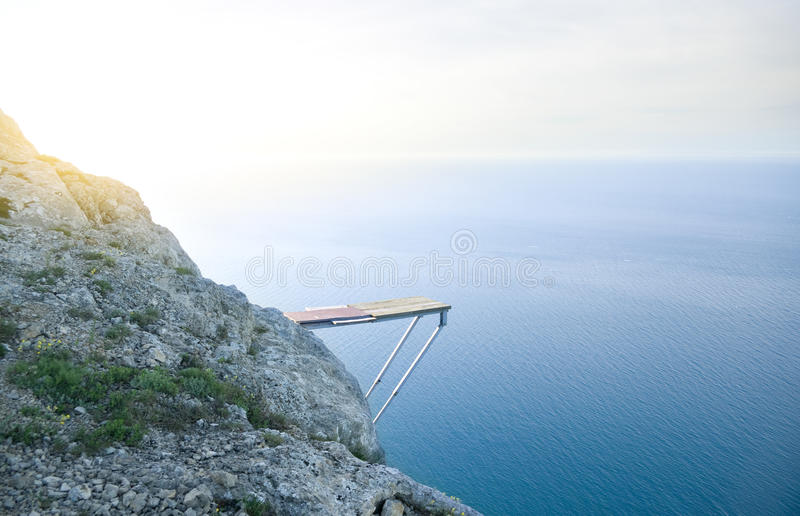 Cliff Into Blue Water stock photography