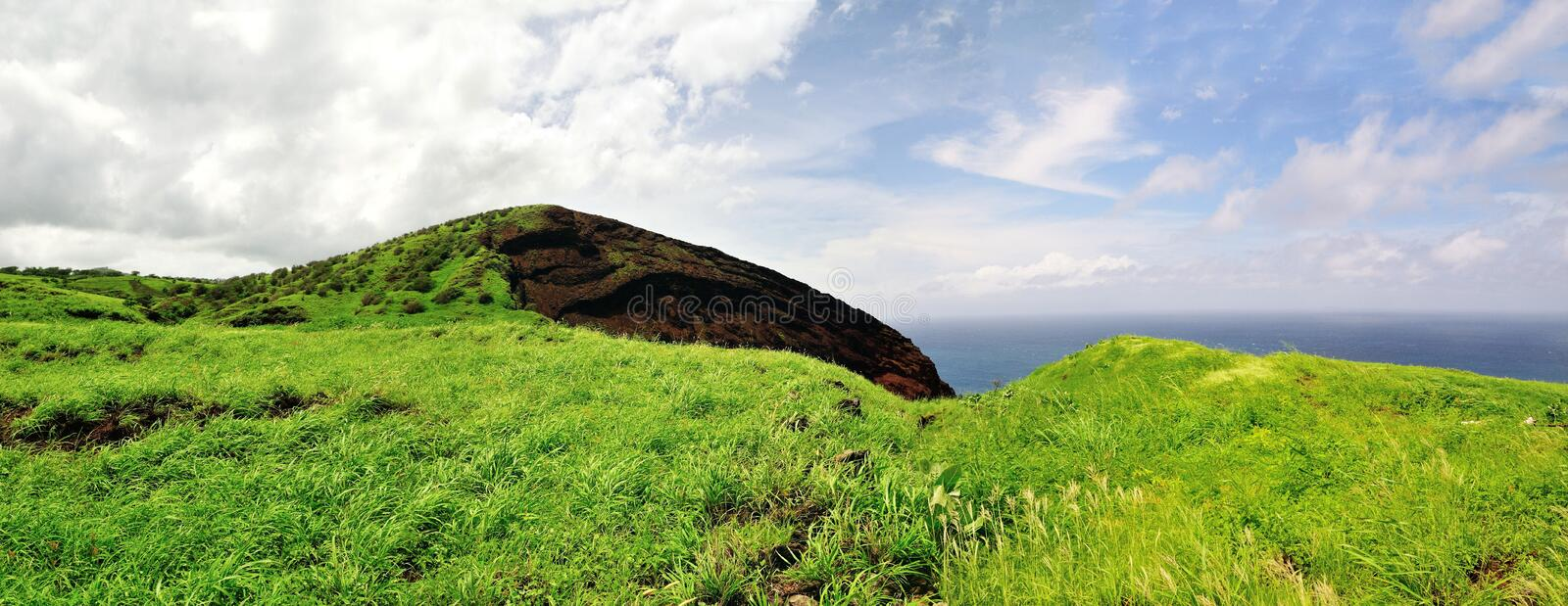 Cliff edge by the ocean. Cliff edge with green grass filed plateau extends over the ocean, on the island of Fogo, in Cabo Verde royalty free stock image