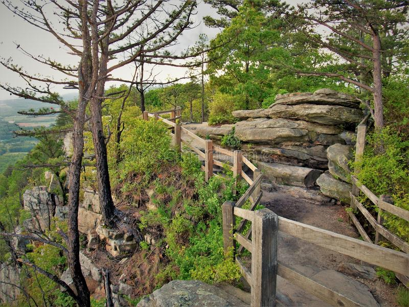 Cliff Edge at Pilot Mountain State Park. A wooden fence provides safety for hikers along a rocky ledge overlooking the surrounding valley at Pilot Mountain State royalty free stock photo