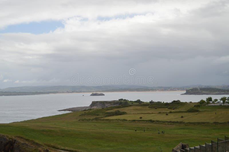 Cliff With een Grote Groene Weide in Santander stock foto