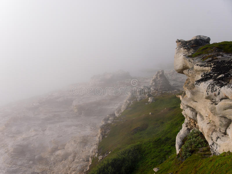 Cliff in the fog stock images