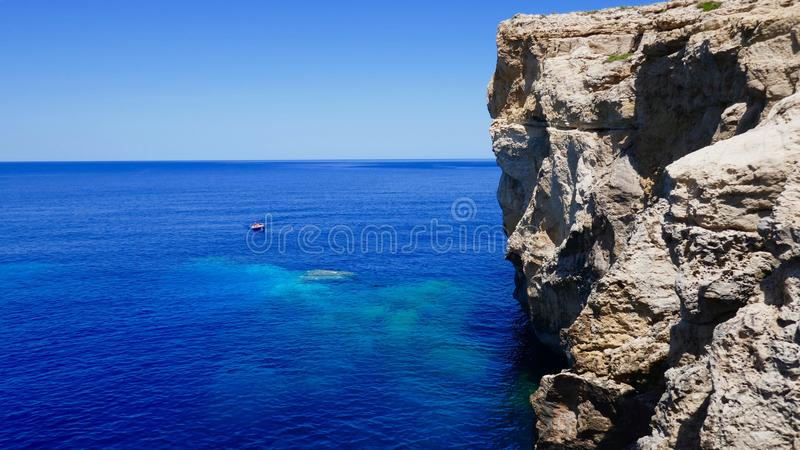 Cliff in Malta with small boath on the azure sea stock photography