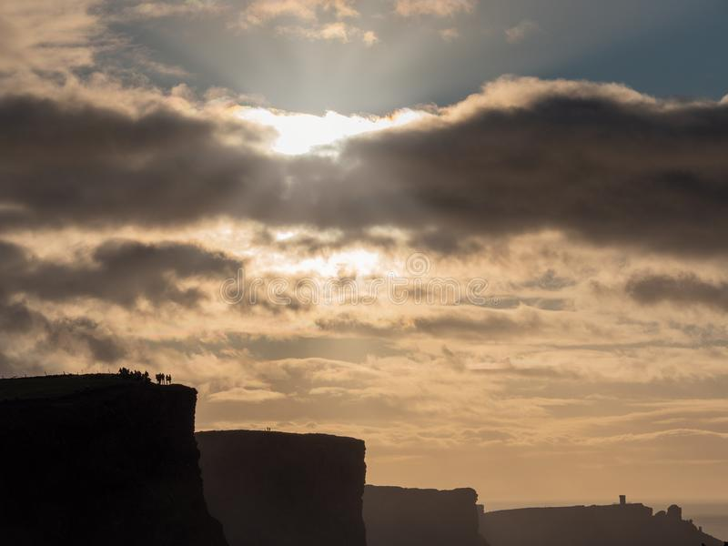 Cliff of Moher silhouette and tourists, Moody sky, sun flare and rays. County Clare, Ireland royalty free stock photography