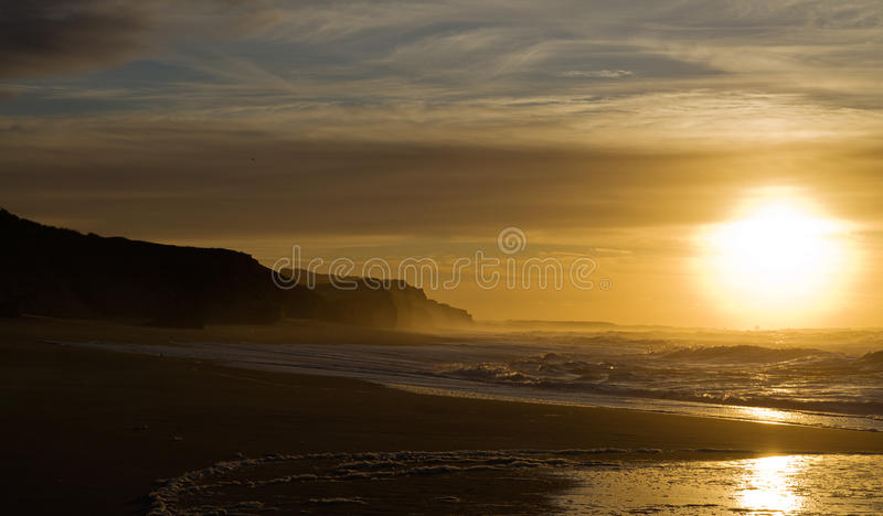 Cliff and ocean waves againt sunset royalty free stock image
