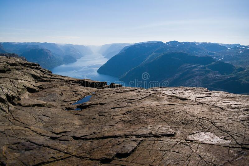 Cliff Preikestolen in Norway. Orange, cracked rocks. Beautiful landscape from a rock shelf stock photos